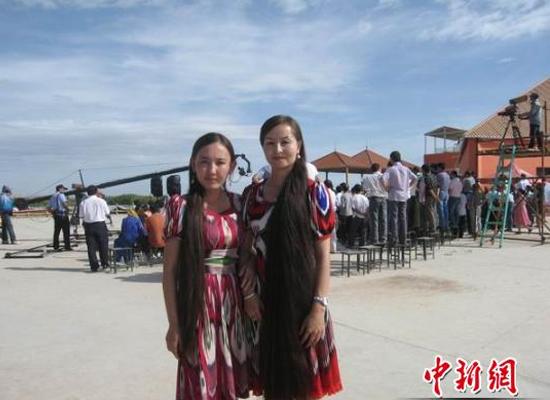 Ngô Nhĩ Khắc Tư (đứng bên phải) cạnh một cô gái tham gia cuộc thi
