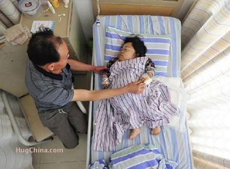 Ông Deng Xinglu chăm sóc cho cô vợ nhỏ bé có chiều cao chỉ bằng đứa trẻ 1 tuổi của mình tại bệnh viện. (Ảnh: HugChina)