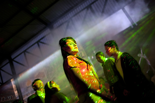 Linda Elizabeth Tylor Martinez, 22, is lit up by lights as she dances after performing at the Quinceanera birthday party of her friend Clancy Azuzena Monroy at a neighborhood dance hall in Guatemala City. Born a man, Tylor is a transgender woman who moves between two distinct worlds: one male, one female. Tylor is a man as a teacher and a woman as a prostitute.