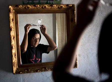 Tylor ngắm mình trong gương và tự đeo chiếc vương miện bằng giấy mà
