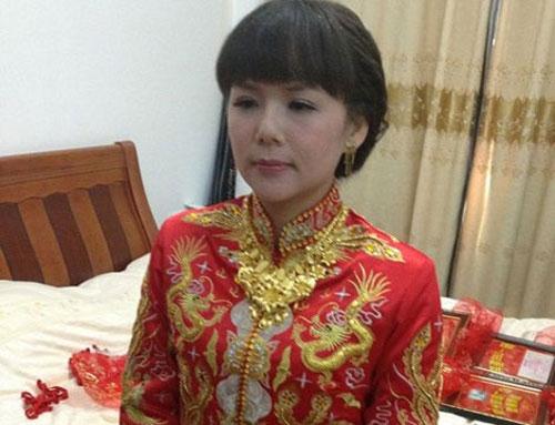 """Con gái của """"đại gia"""" Wu Ruibiao trong trang phục cô dâu và đeo rất nhiều trang sức vàng."""