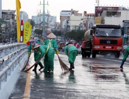 Công nhân đang chùi, rửa mặt đường trước giờ thông xe