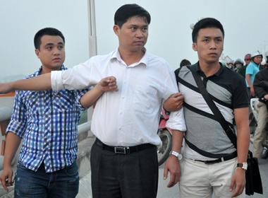 Cơ quan cảnh sát điều tra Công an Hà Nội dẫn giải bác sĩ Nguyễn Mạnh Tường (giữa) đến cầu Thanh Trì (bắc qua sông Hồng) để dựng lại hiện trường vụ việc -