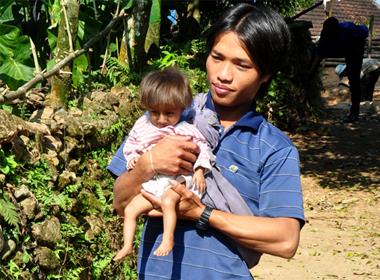 Anh Đinh Văn An ôm con trai tí hon đi trong làng Gò Da, xã Sơn Ba. Ảnh: Trí Tín.