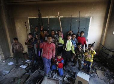 Ảnh thời sự: Trẻ em hớn hở giơ súng trong lớp học đổ nát