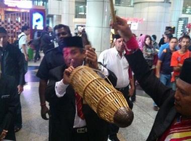Pháp sư Ibrahim Mat Zin hôm qua thực hiện nghi thức tâm linh tại lối vào của Sân bay Quốc tế Kuala Lumpur. Ảnh: Star