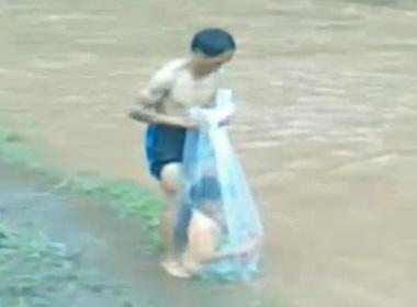 Một học sinh chui vào túi nilông để người lớn kéo qua suối - Ảnh trích từ clip của cô giáo Tòng Thị Minh