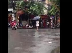 Video lạ lùng thiếu nữ váy trắng đứng 4 tiếng giữa phố mưa Hà Nội