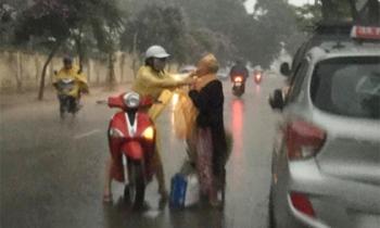 Khoảnh khắc đẹp nhất ngày mưa: Cô gái dừng xe, mặc áo mưa cho cụ bà