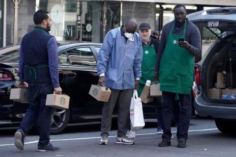 Một nhân viên y tế nhận được một thùng cà phê miễn phí của Starbucks ở Manhattan, ngày 27/3/ 2020.