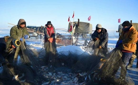 Ngư dân kéo lưới qua một hố thủng trên mặt hồ đóng băng (Ảnh: Xinhua)