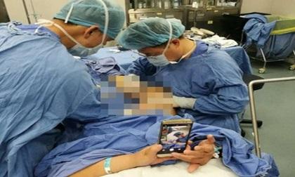 TQ: Bác sĩ mổ chân, bệnh nhân ung dung chơi điện thoại