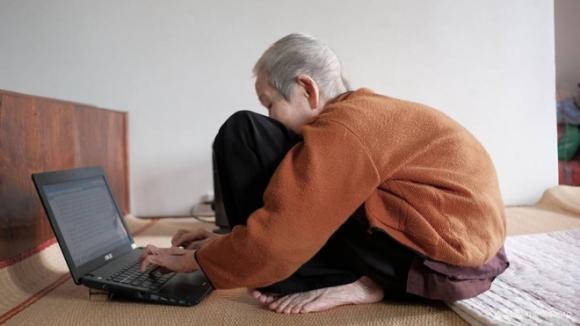 Ở tuổi 97, cụ Thi sử dụng máy tính thành thạo và hàng ngày đều lên mạng đọc tin tức, bình luận trên các diễn đàn. Ảnh: Mediacorp.