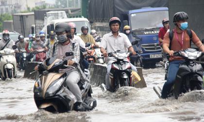 Mưa từ sáng sớm, người Sài Gòn bì bõm lội nước, chen chúc nhau đi làm