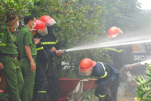 Lực lượng chức năng phun nước dập lửa tại hiện trường