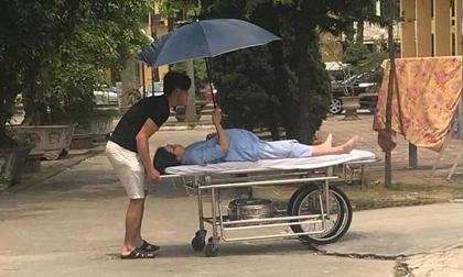 Bức ảnh chồng đẩy xe, vợ bầu nằm cáng vẫn che ô cho chồng khiến cộng đồng mạng dậy sóng