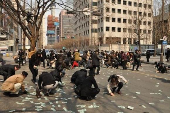 Hàng trăm người mải mê nhặt tiền trên đường phố.