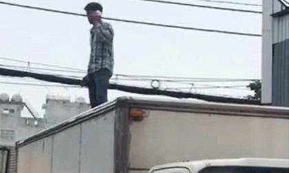 Nam thanh niên nghi 'ngáo đá', tay cầm dao bất ngờ leo lên nóc xe tải đứng nói nhảm