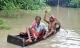 Người châu Á chèo thuyền, bơi phao giữa phố sau mưa lũ